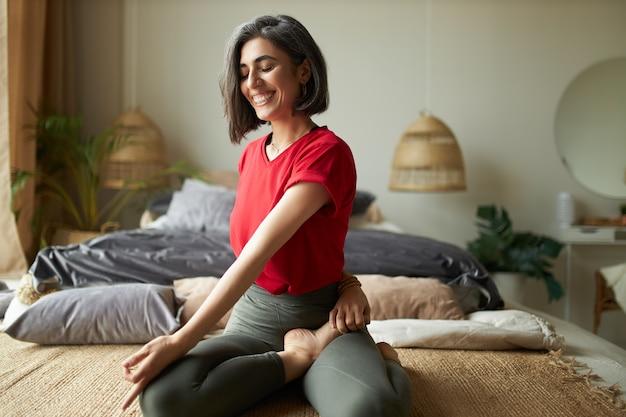 Vrolijke jonge atletische vrouw blootsvoets zittend op tapijt, benen gekruist houden, zittende spinale draai doen tijdens yogales, genieten van rekoefeningen, diep ademhalen, ogen sluiten Gratis Foto