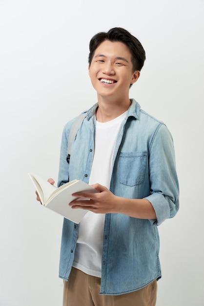 Vrolijke jonge aziatische student met een boek Premium Foto