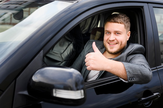 Vrolijke jonge bestuurder die de camera bekijkt Gratis Foto