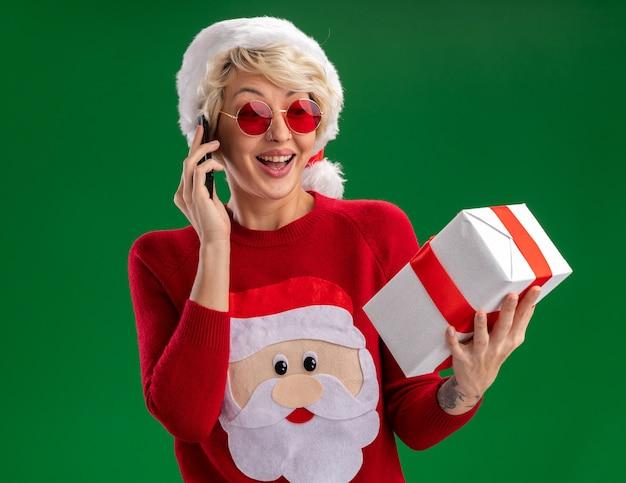 Vrolijke jonge blonde vrouw met kerstmuts en kerstman kersttrui met bril houden en kijken naar geschenkpakket praten over telefoon geïsoleerd op groene muur Gratis Foto