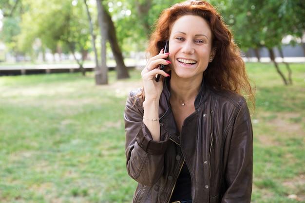 Vrolijke jonge dame die op telefoon in stadspark spreekt Gratis Foto