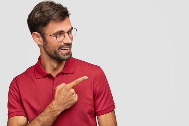 Vrolijke jonge emotionele man die zich voordeed tegen de witte muur Gratis Foto