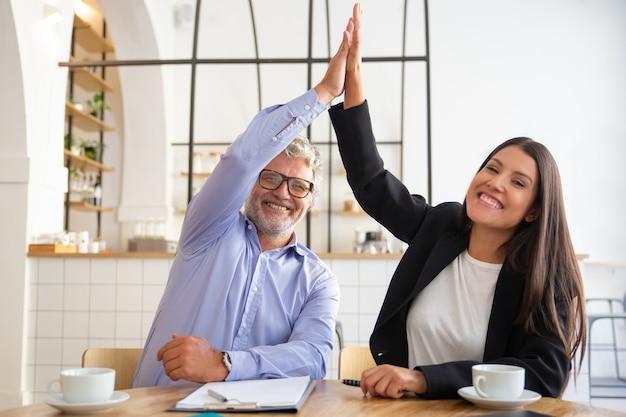 Vrolijke jonge en volwassen zakenpartners geven high five en vieren succes, zittend aan tafel met documenten en koffiekopjes Gratis Foto