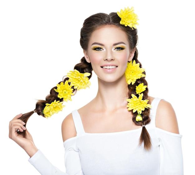 Vrolijke jonge glimlachende mooie vrouw met lange vlechten. mode portret. aantrekkelijk meisje met heldere gele make-up - geïsoleerd op wit. professionele make-up. kunst kapsel. Gratis Foto
