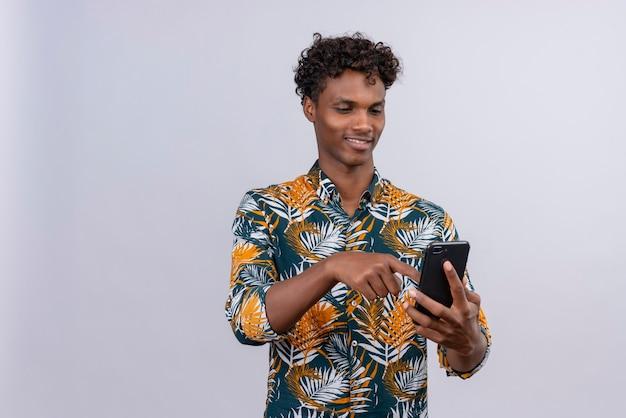 Vrolijke jonge knappe donkerhuidige man met krullend haar in bladeren gedrukte shirt smartphone hand in hand en scherm van mobiele telefoon aan te raken op een witte achtergrond Gratis Foto