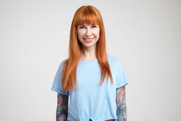 Vrolijke jonge langharige roodharige dame met tatoeages die haar witte perfecte tanden tonen terwijl ze gelukkig lacht naar de camera, geïsoleerd tegen een witte achtergrond Gratis Foto