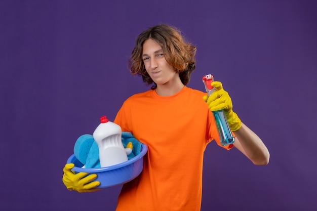 Vrolijke jonge man in oranje t-shirt die rubberen handschoenen draagt ?? die bekken met het schoonmaken van gereedschappen houdt en het schoonmaken van spray positief en gelukkig over paarse ruimte Gratis Foto