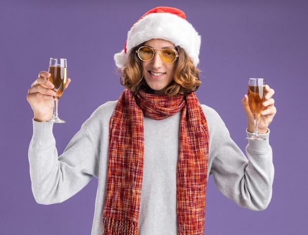 Vrolijke, jonge man, met, kerstmuts, en, gele bril, met, warme sjaal om zijn, nek, vasthouden, glazen champagne, kijken naar, camera glimlachen, vrolijk, staand, op, paarse achtergrond Gratis Foto