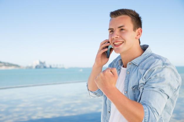 Vrolijke jonge man praten over telefoon en tonen wining gebaar Gratis Foto