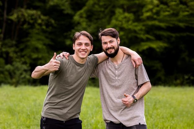 Vrolijke jonge mannen die voortreffelijkheidsteken op open plek tonen Gratis Foto