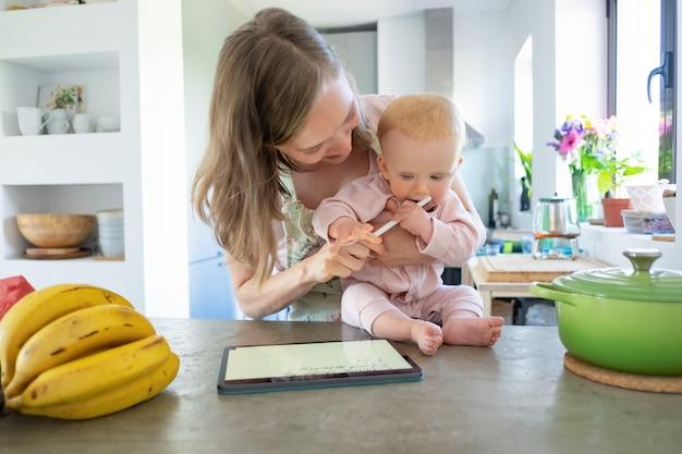 Vrolijke jonge moeder en baby dochter samen koken thuis, kijken naar recepten op pad, met behulp van tablet. kinderopvang of koken thuis concept Gratis Foto