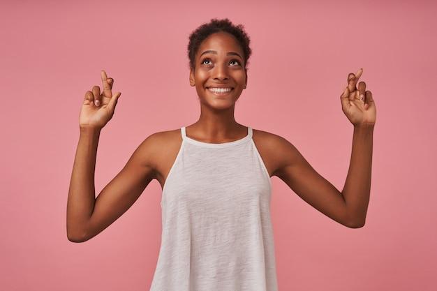 Vrolijke jonge mooie bruinharige krullende vrouw met breed lachend terwijl ze naar boven kijkt en haar vingers gekruist houdt, geïsoleerd over roze muur Gratis Foto