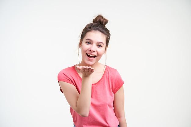Vrolijke jonge mooie bruinharige vrouw met knot kapsel houden opgeheven hand voor haar gezicht en vrolijk kijken naar camera, geïsoleerd op witte achtergrond Gratis Foto