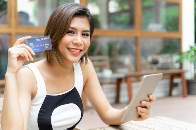 Vrolijke jonge mooie vrouw gebruikte cradit-kaart Gratis Foto