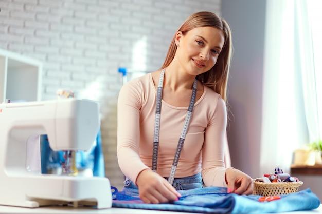 Vrolijke jonge naaister zitten aan de werktafel in haar kantoor Premium Foto