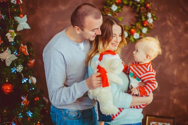 Vrolijke jonge ouders houden een klein kind poseren voor een kerstboom Gratis Foto