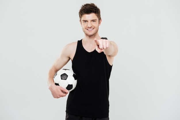 Vrolijke jonge sportman met voetbal staande geïsoleerd op witte achtergrond. kijkend naar camera wijzen. Gratis Foto