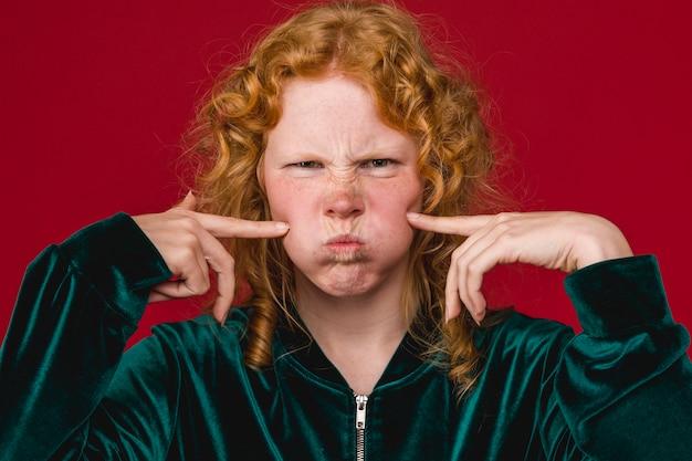 Vrolijke jonge vrouw blazen en wangen drukken Gratis Foto