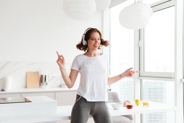Vrolijke jonge vrouw dansen luisteren muziek. Gratis Foto