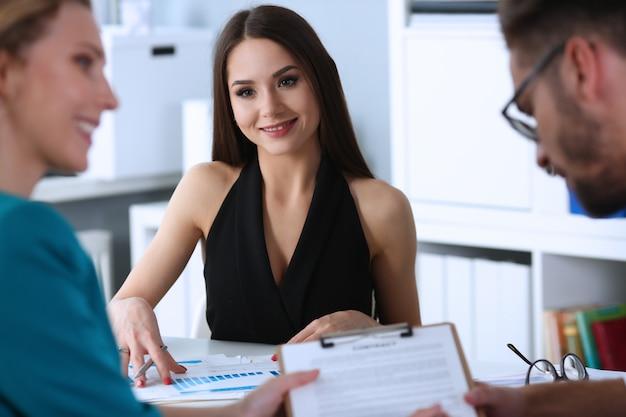 Vrolijke jonge vrouw die haar collega's bekijkt Premium Foto