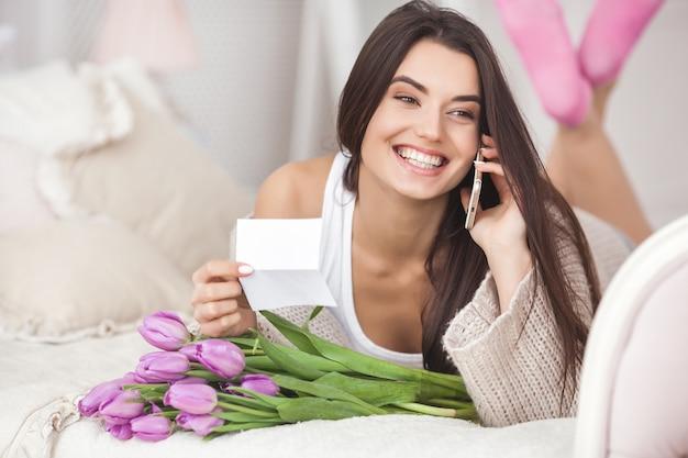 Vrolijke jonge vrouw die op de telefoon spreekt en bloemen houdt. mooie dame met tulpen Premium Foto