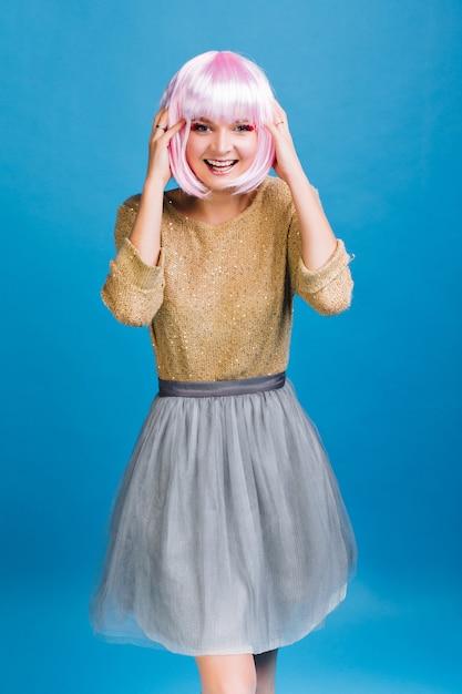 Vrolijke jonge vrouw in gouden heldere trui, grijze tule rok met roze geknipt haar met plezier op blauwe ruimte. Gratis Foto