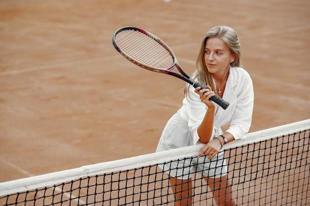 Vrolijke jonge vrouw in t-shirt. vrouw met tennisracket en bal. Gratis Foto