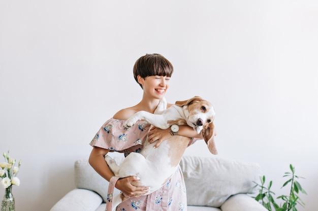 Vrolijke jonge vrouw in trendy polshorloge met haar grote puppy met zwarte neus en lachen Gratis Foto