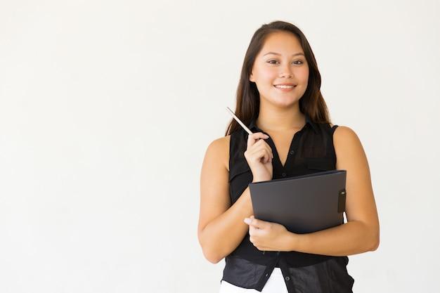 Vrolijke jonge vrouw met map en pen Gratis Foto