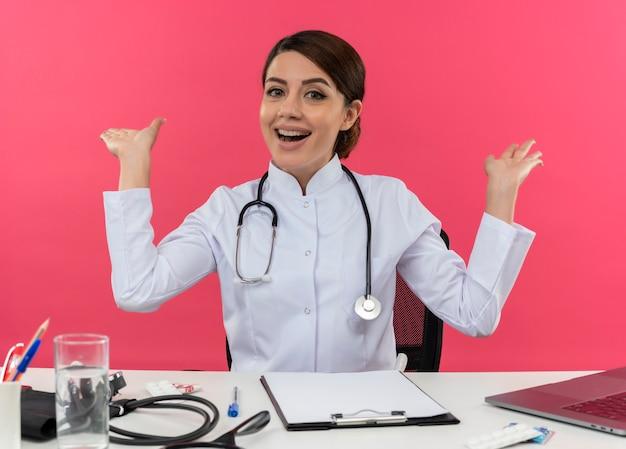 Vrolijke jonge vrouwelijke arts die medische mantel draagt met een stethoscoop zittend aan een bureau werkt op de computer met medische hulpmiddelen spreidt handen op geïsoleerde roze muur met kopie ruimte Gratis Foto
