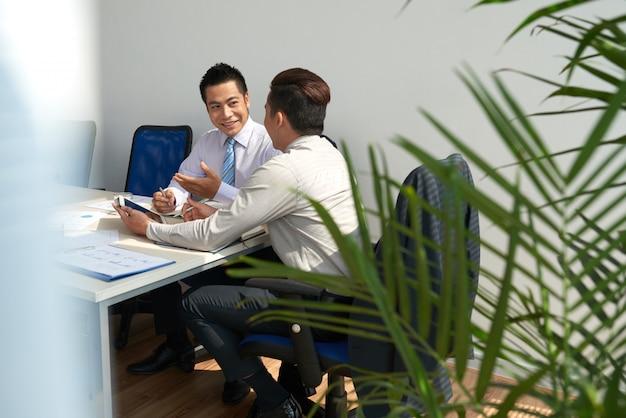 Vrolijke jonge zakenlieden die het werk plannen op de vergadering Gratis Foto