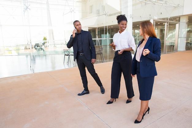 Vrolijke kantoorcollega's lopen over lobby en chatten Gratis Foto