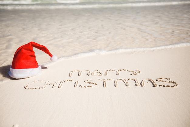 Vrolijke kerstmis die op tropisch strand wit zand wordt geschreven met kerstmishoed Premium Foto