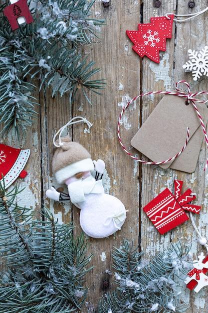Vrolijke kerstmis en gelukkige vakantie wenskaart, frame, banner. nieuwjaar. nieuwjaarskaart met sneeuw op houten achtergrond. winter xmas vakantie thema. plat leggen. Premium Foto