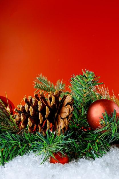 Vrolijke kerstmis en nieuwjaar decoratie sneeuw winter in de bal sneeuwvlokken op tak met dennenappel Premium Foto