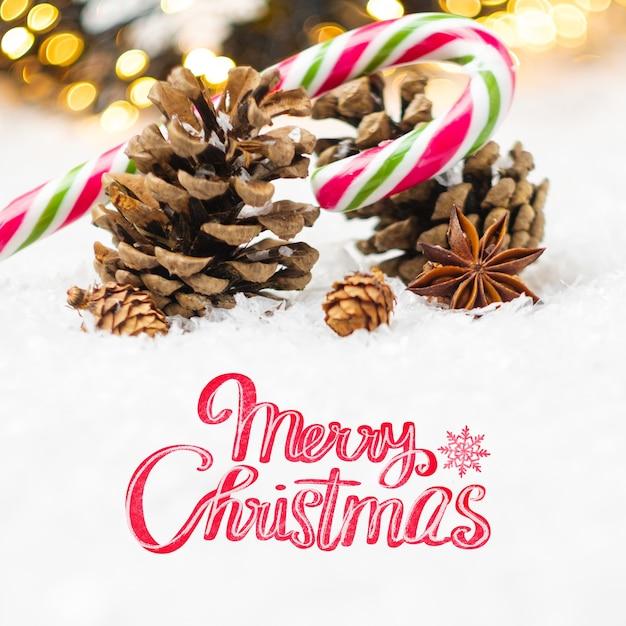 Vrolijke kerstmistekst met de kegel van het suikergoedstokje in de sneeuw Premium Foto