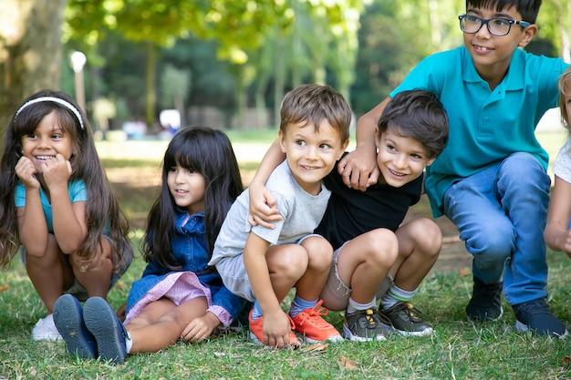 Vrolijke kinderen zitten en gehurkt op het gras, knuffelen elkaar en kijken opgewonden weg. kinderen spelen of entertainment concept Gratis Foto