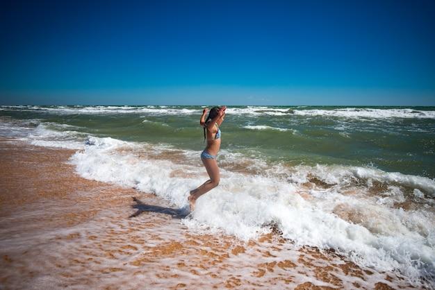 Vrolijke kleine actieve meisje springen op de golven van een stormachtige zee op een zonnige warme zomerdag Premium Foto