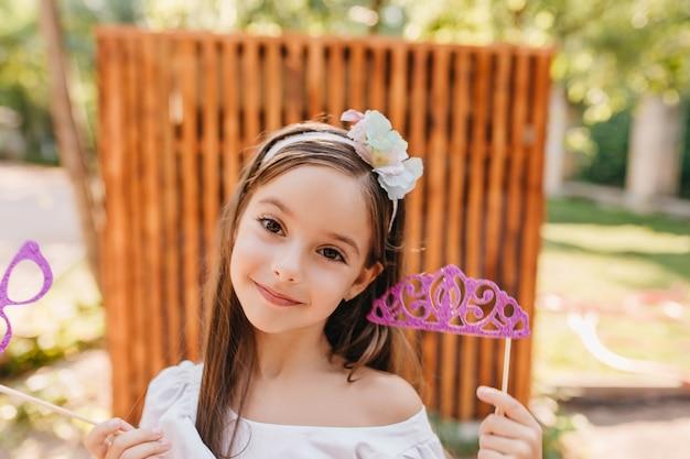Vrolijke kleine dame met grote bruine ogen roze speelgoedkroon vasthouden en poseren in de tuin met plezier. openluchtclose-upportret van glimlachend donkerbruin meisje met in hand fonkelingsglazen. Gratis Foto