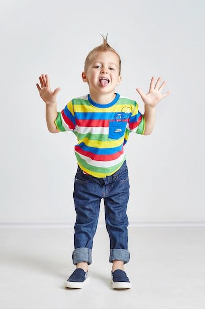 Vrolijke kleine jongen hamming en tonen van de tong Premium Foto