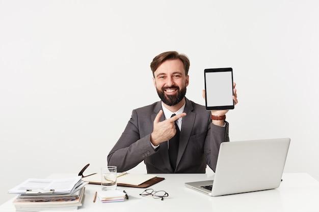 Vrolijke knappe jonge brunette man met baard formele kleding dragen over witte muur zittend aan tafel met tablet pc in opgeheven hand, gelukkig op zoek naar voren met brede glimlach Gratis Foto