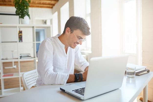 Vrolijke knappe jonge zakenman draagt een wit overhemd op kantoor Gratis Foto
