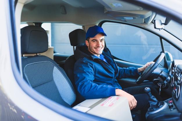Vrolijke koerier in auto die bij camera glimlacht Premium Foto