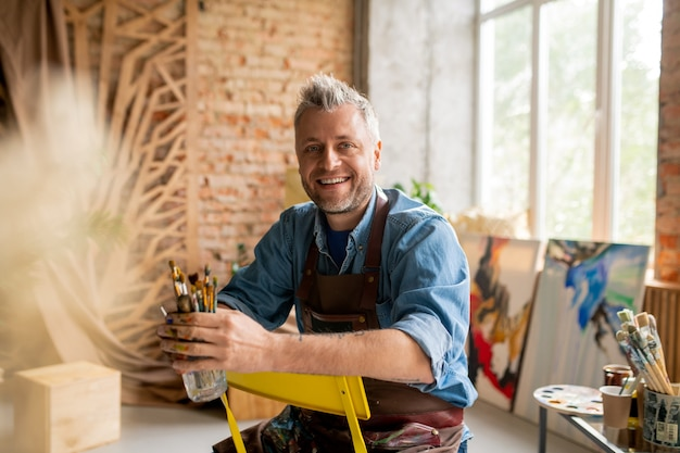 Vrolijke kunstenaar in werkkleding zittend op een stoel Premium Foto