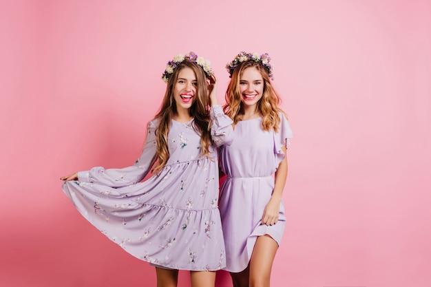 Vrolijke langharige vrouw speelt met haar paarse jurk terwijl poseren met vriend Gratis Foto