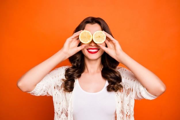 Vrolijke leuke leuke charmante mooie vrouw op zoek in twee helften van citroenen glimlachend toothily stralend. Premium Foto