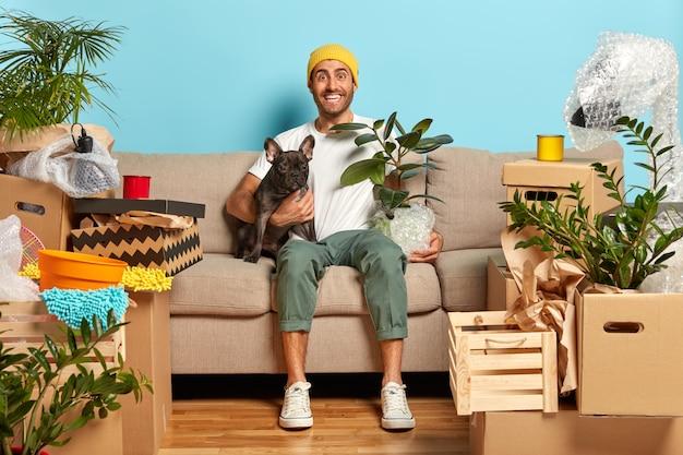 Vrolijke man omhelst hond en pot met kamerplant, zit in de woonkamer op de bank Gratis Foto