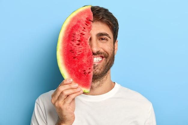 Vrolijke man op een zomerse dag met een plakje watermeloen Gratis Foto