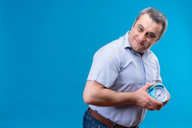 Vrolijke man van middelbare leeftijd in blauw gestreept overhemd met blauwe wekker met handen op een blauwe achtergrond Gratis Foto