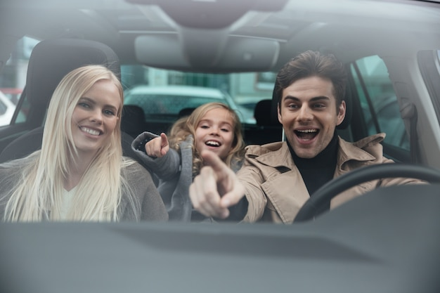 Vrolijke man zit in de auto met zijn vrouw en dochter Gratis Foto